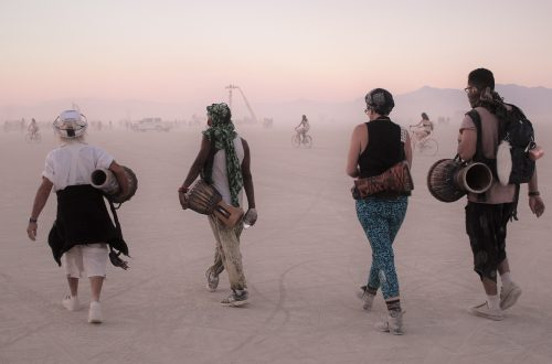 Four people walking while carrying drums at Burning Man