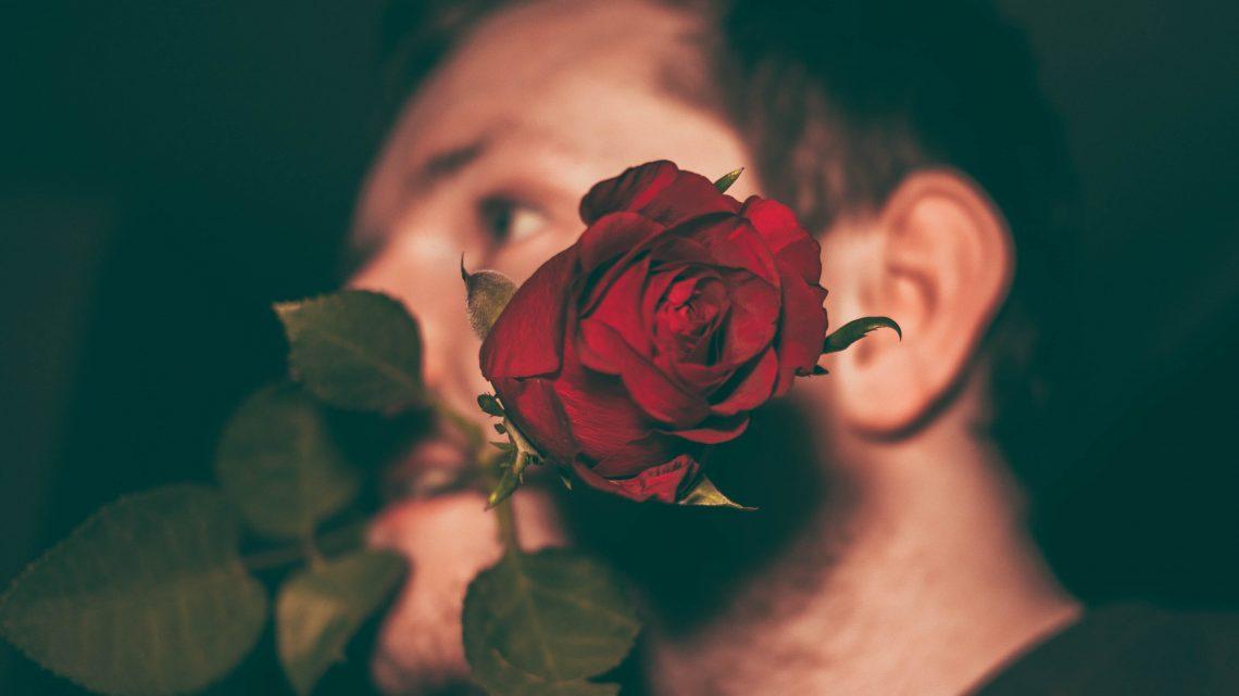 Man biting red rose in closeup shot