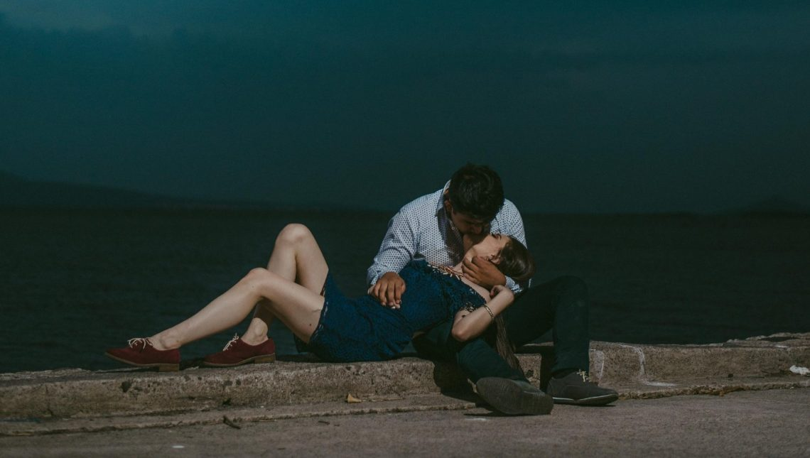 Man kissing woman while sitting on railings during night