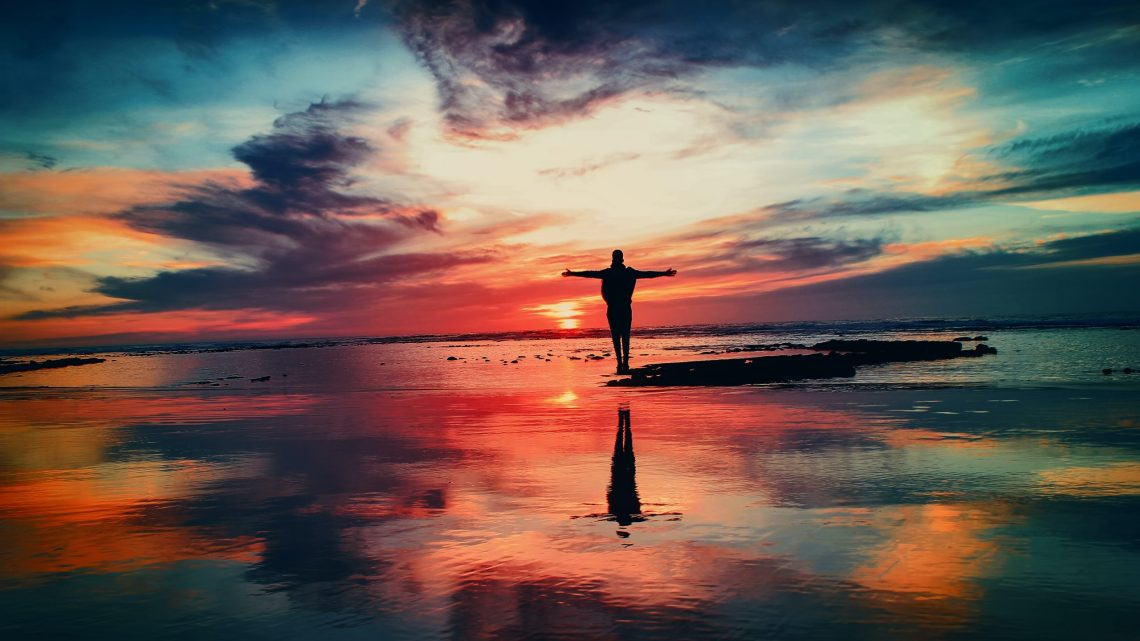 Man Standing near Water at Sunset