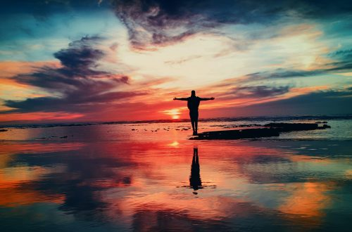 Man Standing near Water at Sunset