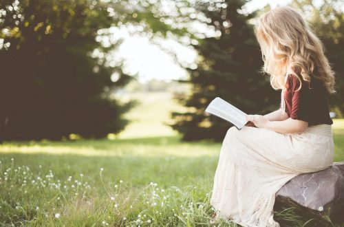 Girl reading and thinking in nature