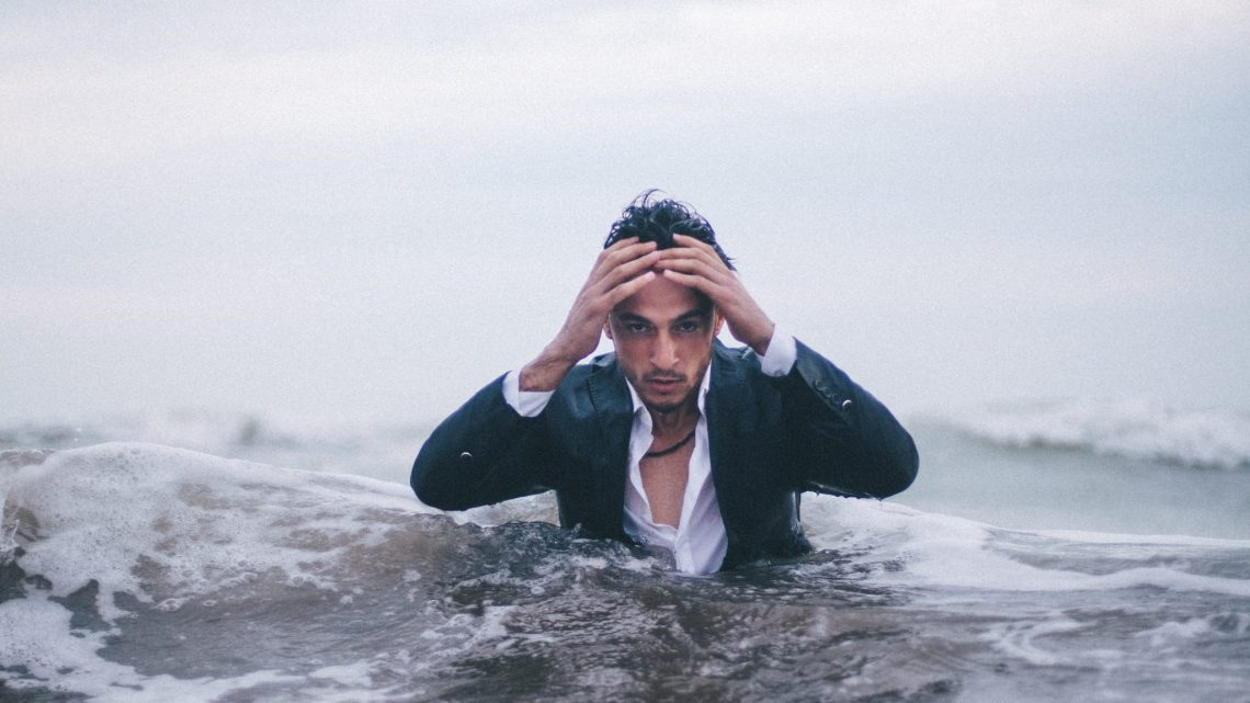 Man dressed in a suit up to his chest in the ocean, holding his head