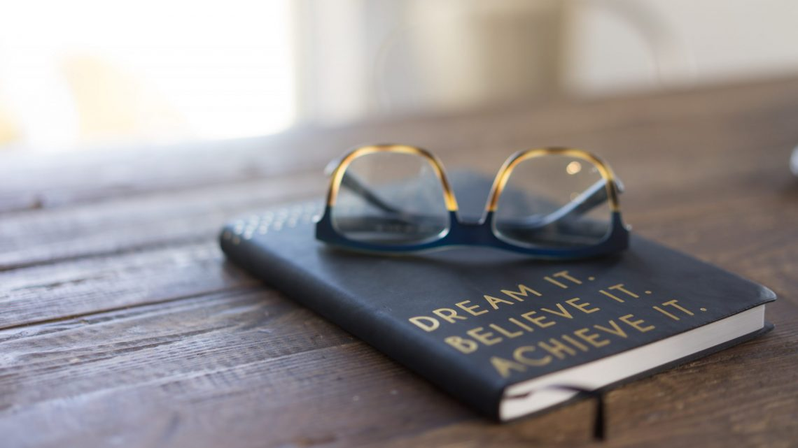 Book - titled Dream, Believe, Achieve - with glasses on top sits on a desk