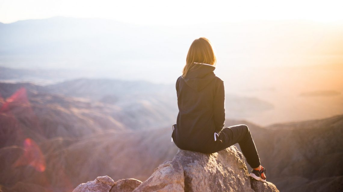 Woman sitting on rocky outcrop looking into the sunset