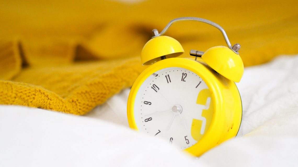 Bright Yellow Alarm Clock on the Bed